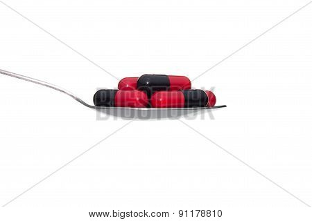 Black Red Medicine Or Capsule On Spoon Isolated On White Background
