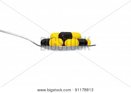 Black Yellow Medicine Or Capsule On Spoon Isolated On White Background