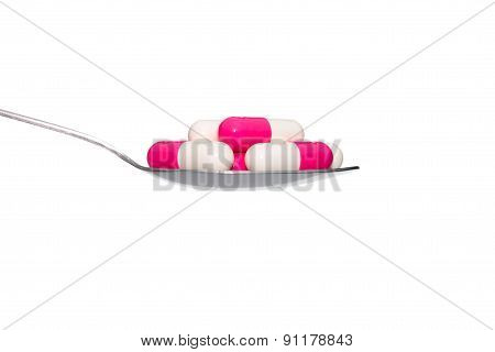 Pink White Medicine Or Capsule On Spoon Isolated On White Background