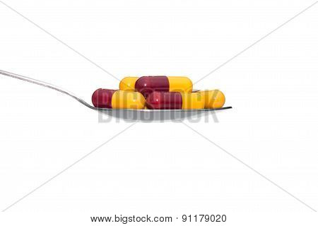 Red Yellow Medicine Or Capsule On Spoon Isolated On White Background