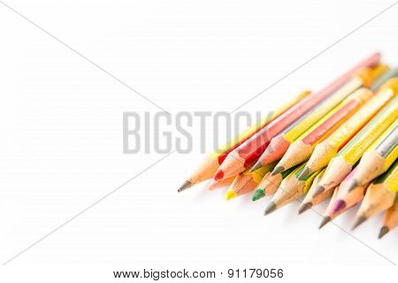 Old pencils in row on cleared white background
