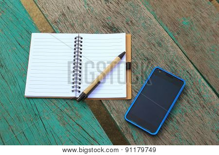 Notebook With Pen And Mobile Phone On The Green Table