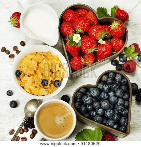 Healthy Breakfast with coffee, corn flakes, milk and berry on old wooden background. Health and diet concept