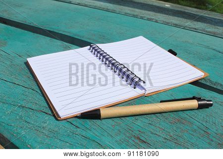 Notebook On The Green Table