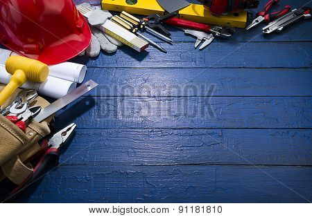 Construction equipments on blue wood background with spot lightened space for your text. Blueprints are not subject to copyright. Words on them are regular like kitchen, bedroom, bathroom etc.