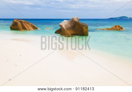 Beautifully shaped granite boulders and a perfect white sand at Anse Gaulettes, La Digue island, Seychelles. Long exposure