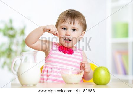 happy kid girl eating food itself with spoon
