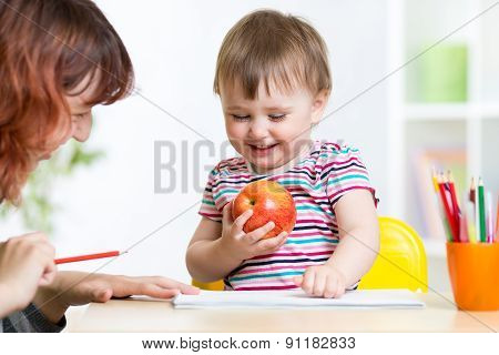 happy child and mother draw with colorful pencils