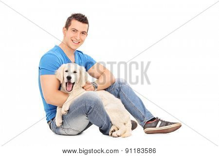 Cheerful young man posing with a cute little Labrador puppy and looking at the camera isolated on white background