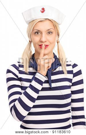 Vertical shot of a beautiful blond woman in sailor outfit holding finger on her lips and looking at the camera isolated on white background