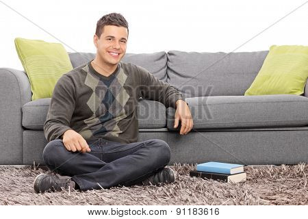 Relaxed young guy sitting on the floor in front of a gray sofa with a couple of books beside him isolated on white background