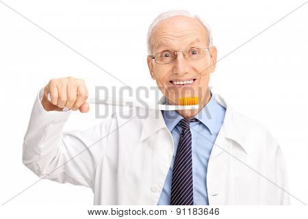 Studio shot of a cheerful mature dentist holding a huge toothbrush and looking at the camera isolated on white background