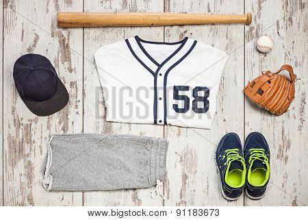 Bunch of sportswear and baseball equipment on a white hardwood floor