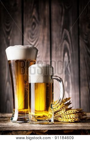Glass and a mug of light beer with foam and ears