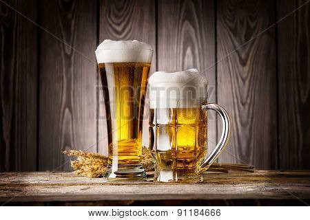 Tall glass and mug of light beer with ears barley