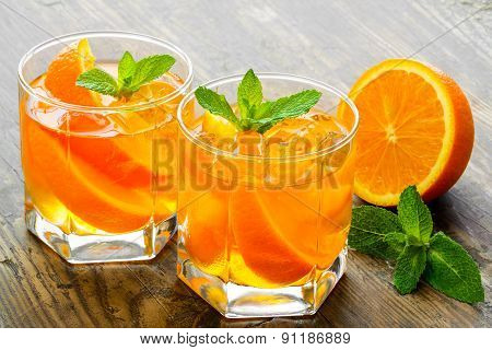 Cocktail. Orange juice with  mint and ice rustic wooden table