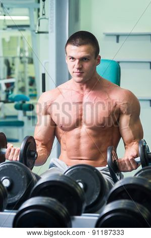 Athlete in the gym. Muscled doing exercises with dumbbells.