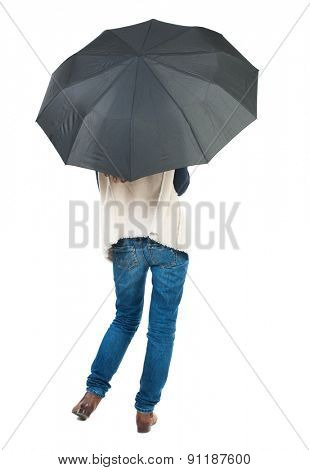 young woman under an umbrella. Rear view people collection.  backside view of person.  Isolated over white background. The girl with long legs hiding under a black umbrella.