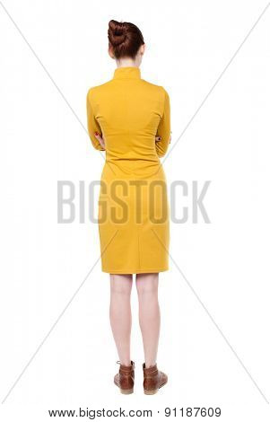 back view of standing young beautiful  woman.  Rear view people collection.  backside of person.  Isolated over white background. Girl in mustard strict dress standing with his arms crossed.