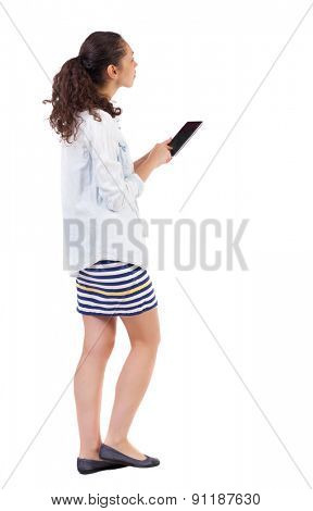 a side view of a woman walking with a tablet PC is in hands of beautiful curly girl in motion.  Rear view people collection. Isolated over white background.  African-American woman is holding a tablet
