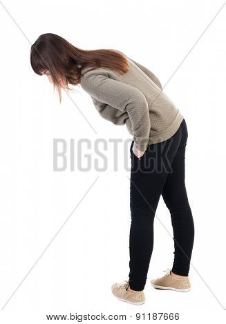 back view standing young beautiful  woman in jeans looks down. Rear view people collection. backside view person.  Isolated over white background. girl looks at his feet with his hands in his pockets