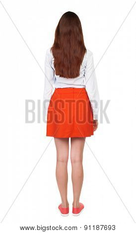 back view of standing young beautiful  woman in dress.  Rear view people collection.  backside view of person.  Isolated over white background. woman in a red skirt standing with her hands along body.