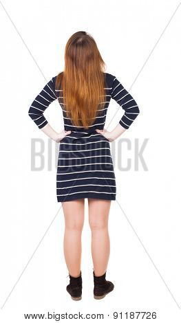 back view of standing young beautiful  woman in dress.  Rear view people collection. backside view of person. Isolated over white background. Adding putting hands on waist stands and looks up.