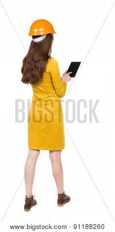Backview business woman in construction helmet stands and enjoys tablet or using mobile phone.  backside view person.  Isolated over white background. girl in yellow dress engineer working with tablet