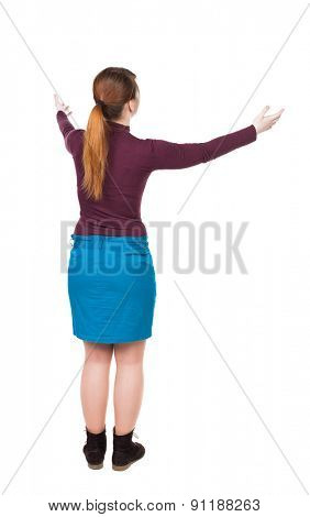 Back view of Beautiful woman in dress looking at wall and Holds  hand up.  Rear view people. Isolated over white background. Young woman in prayer. Joyful girl greets someone hands wide apart.