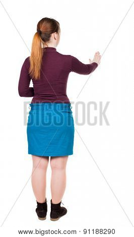back view of young woman presses down on something. Isolated over white background. Rear view people collection. backside view of person. Low girl in a blue skirt looks ahead.