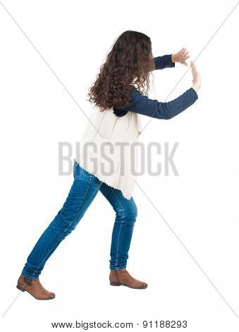 back view of woman pushes wall. Isolated over white background. Rear view people collection. backside view of person.  A girl in a white tank top is pushing the wall in front of him.