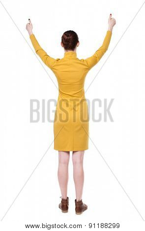 Back view of  woman thumbs up. Rear view people collection. backside view of person. Isolated over white background. Girl in mustard strict dress shows thumb with both hands.