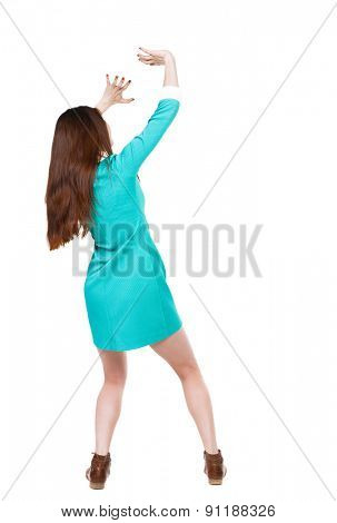 back view woman in dress protects hands from what is falling from above.  backside view of person.  Isolated over white background. girl in blue dress with brown shoes covers her face from the sun.