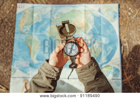 Traveler Searching Direction With A Compass On Background Of Map