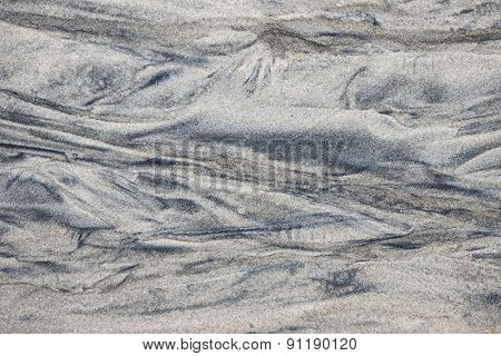 Abstract background of wet sand texture formed by flowing water on beach