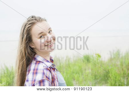 Candid shot of smiling young blond woman on empty beach in plaid shirt with copy space