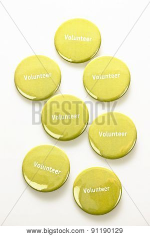 Several green volunteer buttons on white background