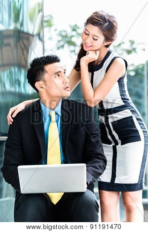 Asian business woman sexually harassing man in public
