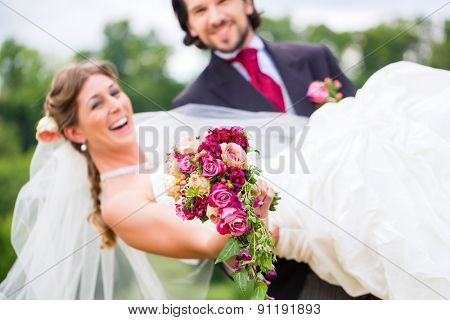 Wedding groom carrying bride on arms
