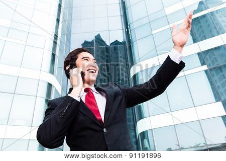 Asian businessman telephoning with smartphone in front of tower building