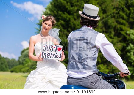 Wedding groom pick up bride with motor scooter having fun