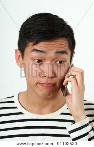 Funny young Asian man using a smartphone.
