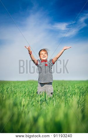 Happy smiling girl jumping at the field of wheat