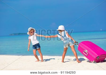 Little adorable girls with big suitcase on tropical white beach