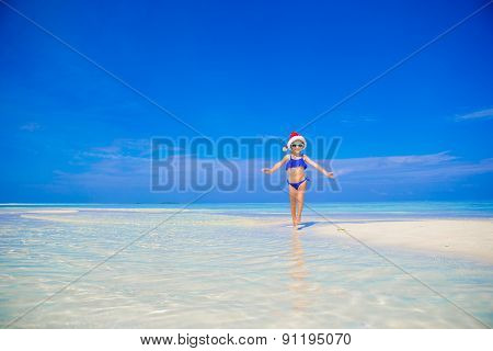 Happy little girl in Santa hat on the beach during vacation