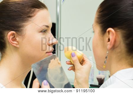 Makeup artist in a beauty salon doing make-up special brush.