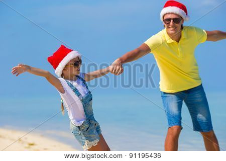 Little girl and happy dad in Santa Hat during beach vacation