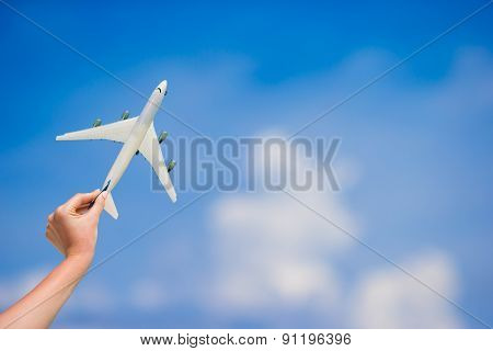 Small white miniature of an airplane on background of blue sky