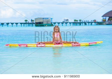 Little adorable girl on a surfboard in the turquoise sea