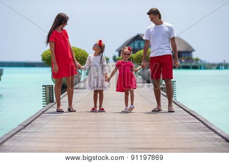 Beautiful family have fun on wooden jetty during summer vacation